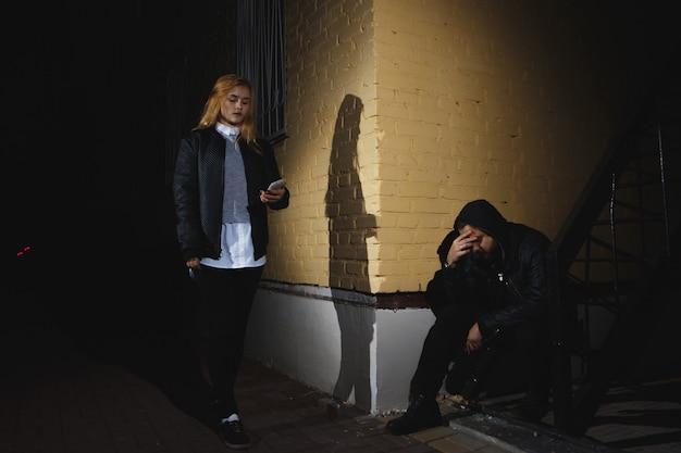 Silhouette eines mannes greift eine frau in einem dunklen tunnel von hinten an. gewalt gegen frauen-konzept. platz kopieren