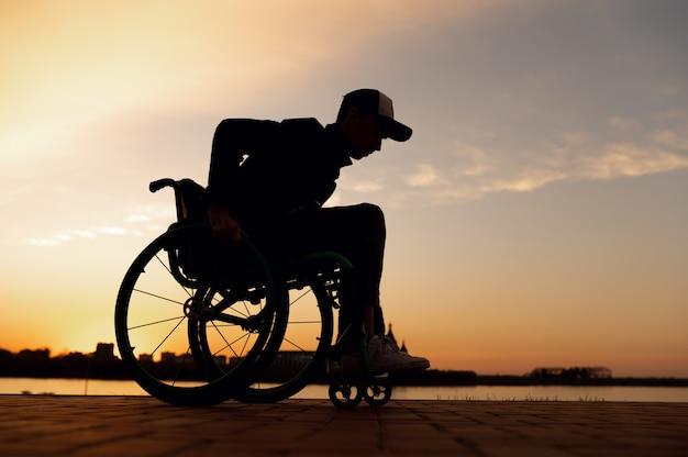Silhouette eines mannes im rollstuhl auf dem hintergrund des hochwertigen fotos des sonnenuntergangs