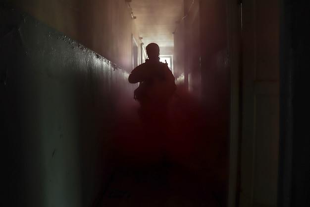 Silhouette eines mannes in uniform mit einer waffe in einem alten korridor in rotem rauch
