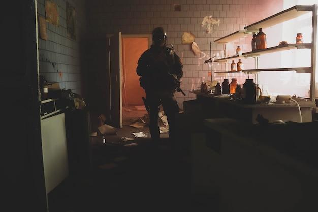 Silhouette eines mannes in uniform mit einer waffe in einem alten zimmer in rotem rauch