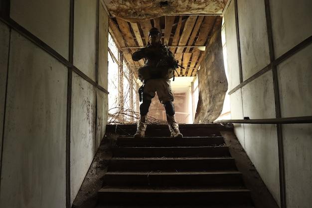 Silhouette eines mannes in uniform mit einer waffe in einer alten treppe in einem glaskorridor in rotem rauch