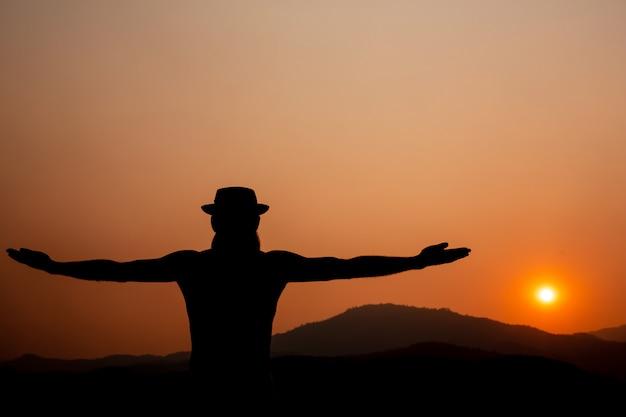 Silhouette eines mannes mit ausgestreckten armen.