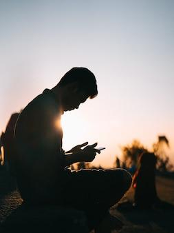 Silhouette eines mannes mit seinem telefon