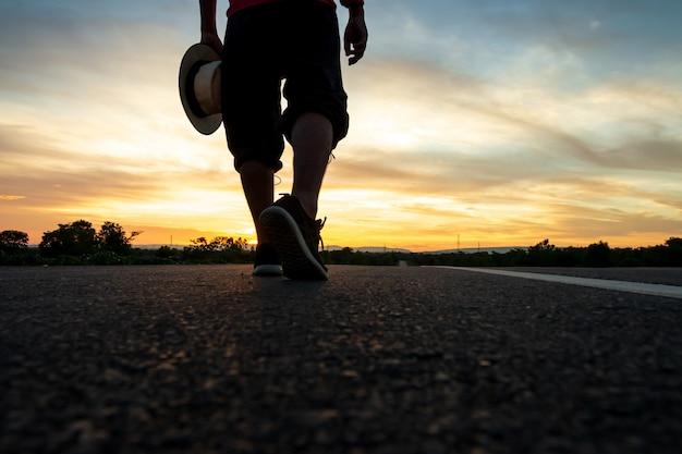 Silhouette eines mannes zu fuß auf der autobahn zum zeitpunkt des sonnenuntergangs