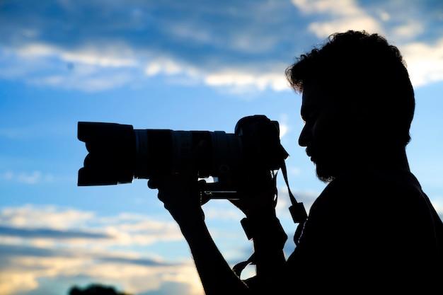 Silhouette eines mannfotografen mit dslr-kamera beim fotografieren bei sonnenuntergang
