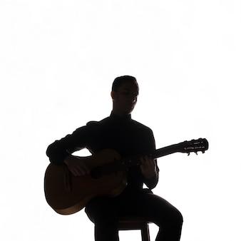 Silhouette eines musikers, der gitarre spielt
