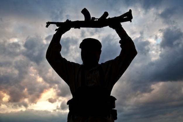 Silhouette eines muslimischen militanten mit gewehr