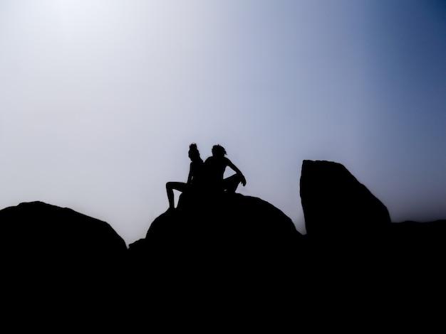 Silhouette eines paares, das auf dem gipfel eines berges sitzt