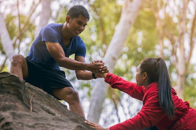 Silhouette eines trailrunners mit der hand, die sich gegenseitig hilft, zusammen einen berggipfel zu erklimmen
