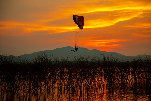 Silhouette fliegende vögel und motorschirm sonnenuntergang himmel