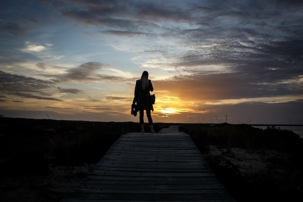 Silhouette frau, die landschaft bei sonnenuntergang fotografiert