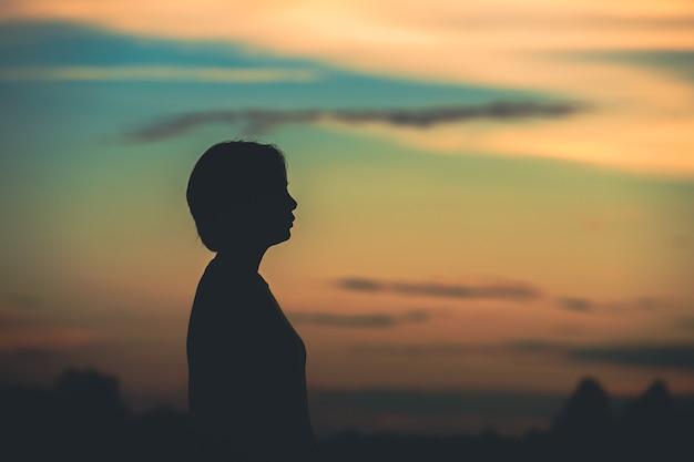 Silhouette frau mit traurigkeit bei sonnenuntergang allein.