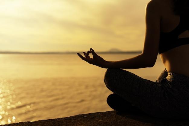 Silhouette frauen üben am morgen yoga am stausee.
