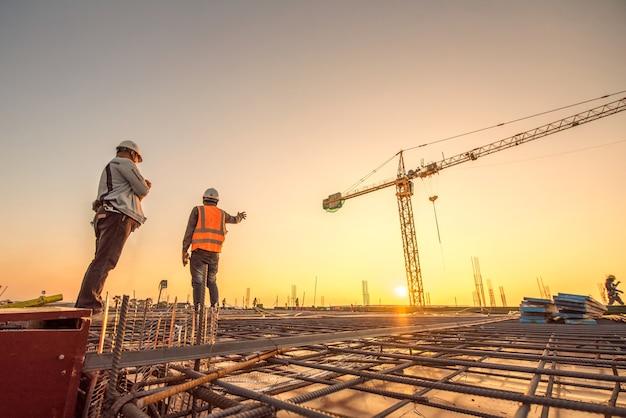 Silhouette-gruppe von arbeiter und bauingenieur in sicherheitsuniform installieren verstärkten stahl