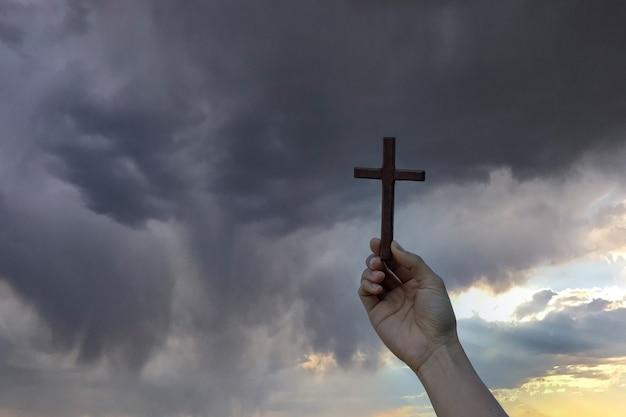 Silhouette hand hält holzkreuz gegen sonnenaufgang, offene handfläche anbetung, beten um segen von gott. christliche religion, kruzifix und glaubenskonzept