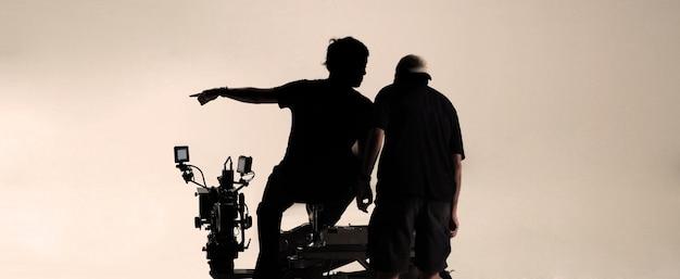 Silhouette hinter den kulissen von kameramann und produktionsteam, die über aufnahmewinkel sprechen
