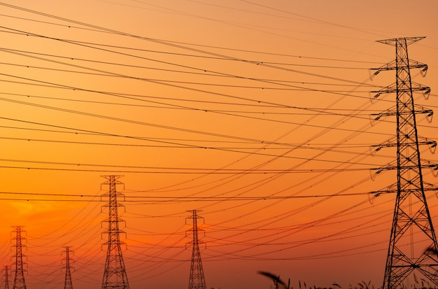Silhouette hochspannungs-strommast und elektrischer draht mit einem orange himmel. strommasten bei sonnenuntergang.
