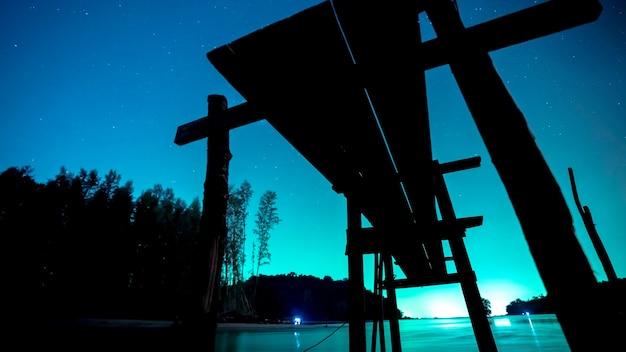 Silhouette holzbrücke mit meer landschaft in der nacht