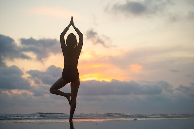 Silhouette junge frau, die yoga lotus position praktiziert, meditiert, strand