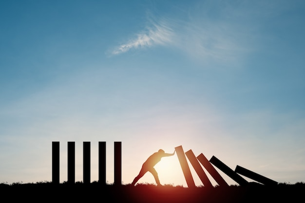 Silhouette mann, der rechteckblock drückt, der fällt, um andere rechtecke zu stoppen, die mit blauem himmel stehen. risiko- und krisenmanagementkonzept.