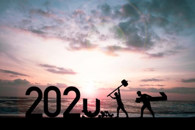 Silhouette mann zerschmettert 2020 jahr und ein mann trägt nummer eins, um 2021 jahr vorzubereiten.