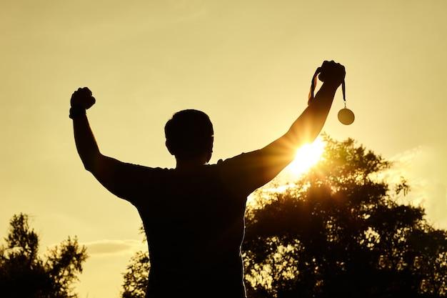 Silhouette menschen sieg hände heben und goldmedaille mit sonnenuntergang himmel halten.