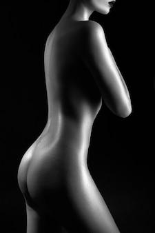 Silhouette nackte frau ist schwarz und weiß, kunst nude pose, heller kontrast schatten auf dem körper des mädchens. perfekter körper und figur