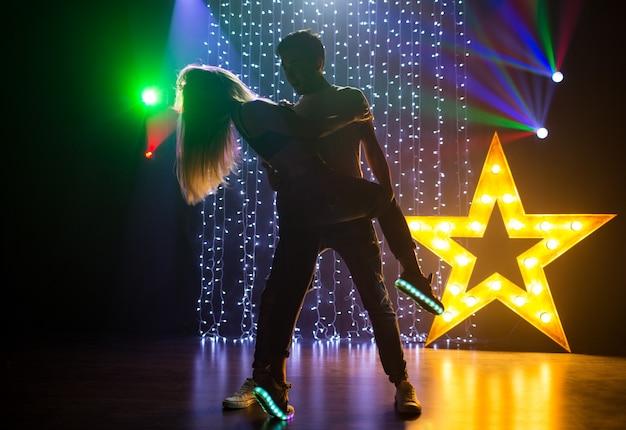 Silhouette paar liebevoller junger mann und frau, die tanzen und spaß in einem nachtclub auf einer party haben