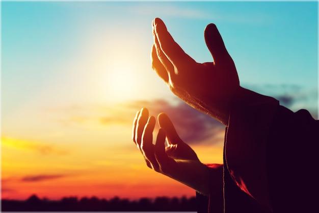 Silhouette rosenkranz gegen kreuz in der hand