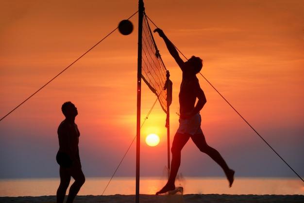 Silhouette spielen beachvolleyball. sonnenuntergang zeit