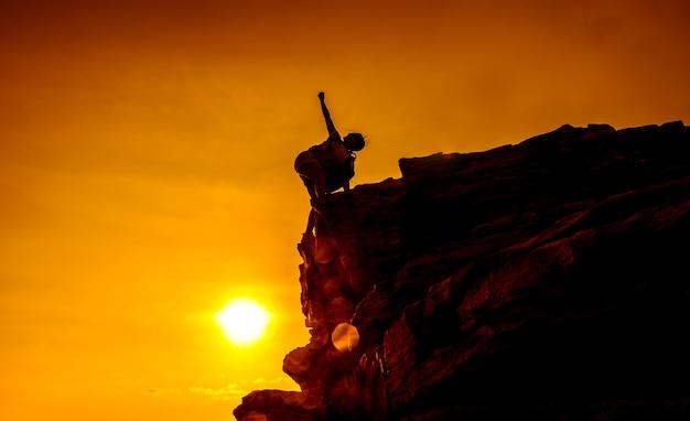 Silhouette sportliche frau auf der klippe. sonnenuntergang und hoher berg. geschäftserfolg und ziel.