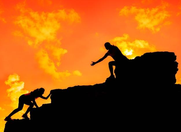 Silhouette sportliche frau, die auf die klippe klettert. business teamwork erfolg und zielkonzept