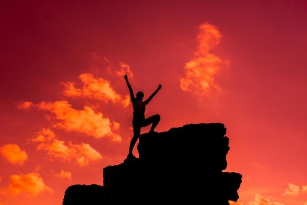 Silhouette sportliche frau, die auf die klippe klettert. erfolgs- und zielkonzept. stark und gesund für outdoor-aktivitäten.