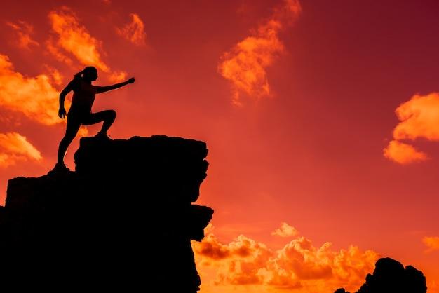 Silhouette sportliche frau, die auf die klippe klettert. geschäftserfolg und zielkonzept. stark und gesund für outdoor-aktivitäten.