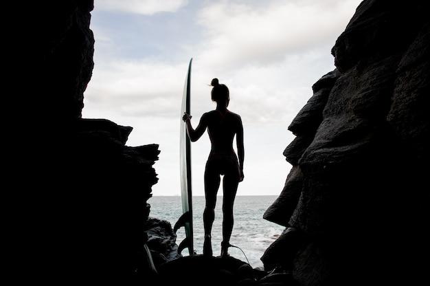 Silhouette sportliches mädchen im badeanzug stehend mit der brandung im felsen am strand atlantik