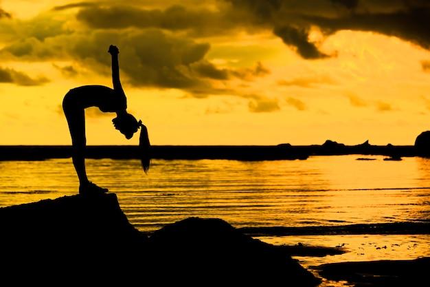 Silhouette-szene der asiatischen frau, die yoga spielt, übung auf felsen in der abenddämmerung am tropischen strand mit sonnenuntergang und reflexion der sonne im meer.