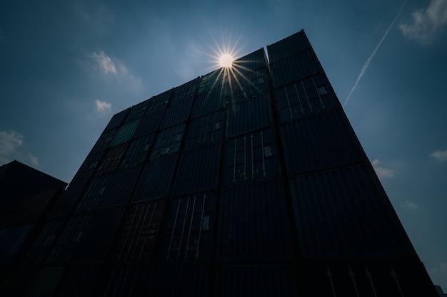 Silhouette versandbehälter mit sonnenflair hellblauer himmelshintergrund weitwinkelaufnahme abgedunkelter schattenton
