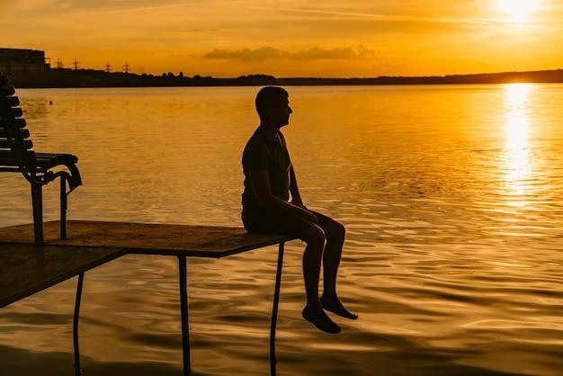 Silhouette von einem schönen mann auf dem mauerwerk über den fluss sitzt
