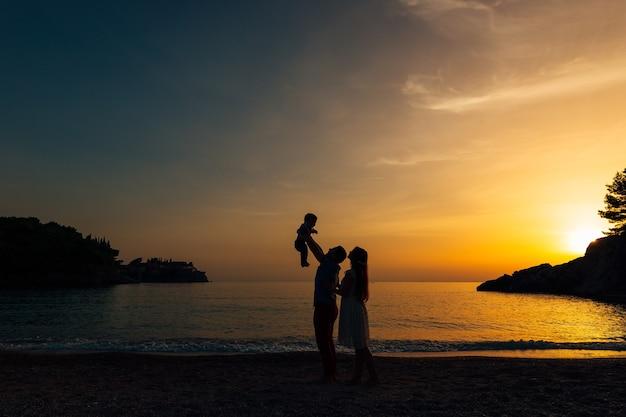 Silhouette von eltern mit einem kind auf see familie am strand