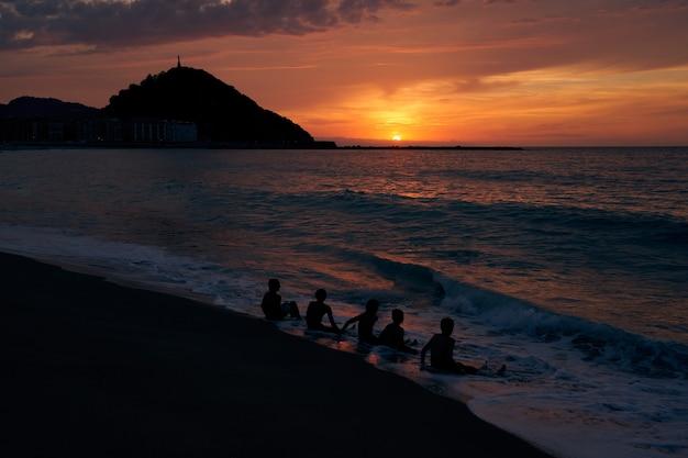 Silhouette von jungen leuten, die bei sonnenuntergang am strand sitzen