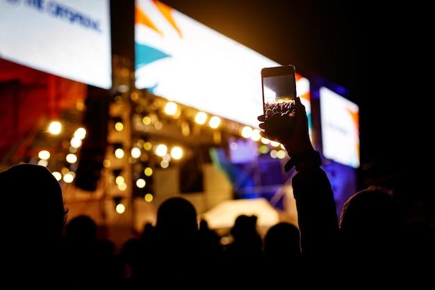 Silhouette von menschen, die ihre smartphones halten und konzert fotografieren.