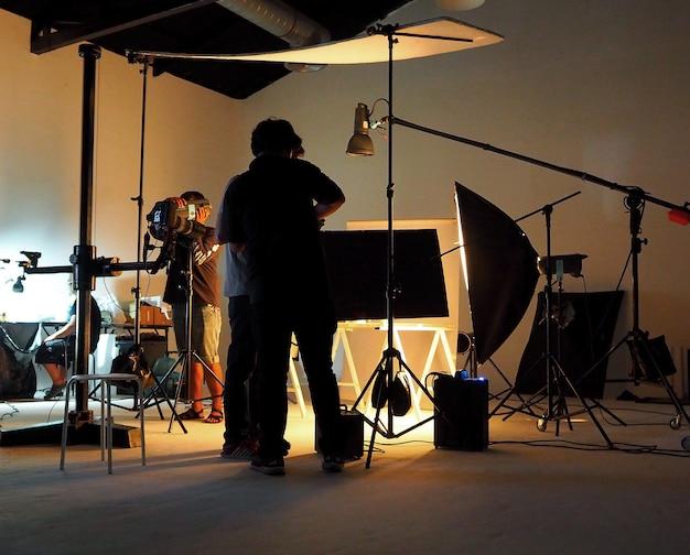 Silhouette von menschen, die im produktionsstudio für das aufnehmen oder aufnehmen durch digitalkamera und beleuchtungsset arbeiten.
