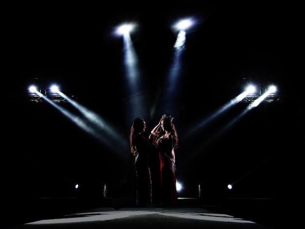 Silhouette von miss beauty contest surround mit licht