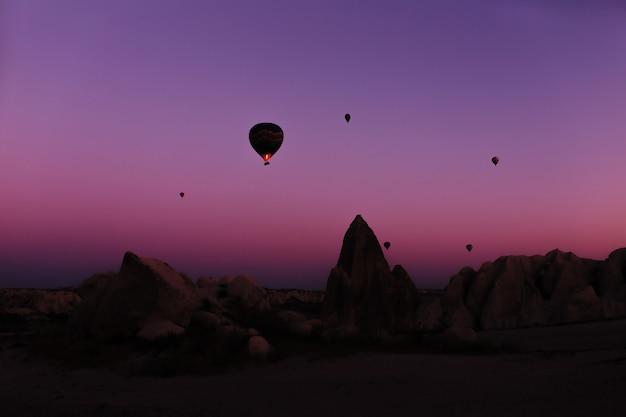 Silhouette von schönen heißluftballons bei sonnenaufgang in kappadokien