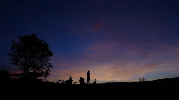 Silhouette von touristen, die im morgenlicht campen