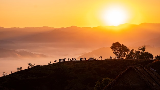 Silhouette von touristen, die in der atmosphäre von nebel und morgensonne im ländlichen thailand eintauchen.