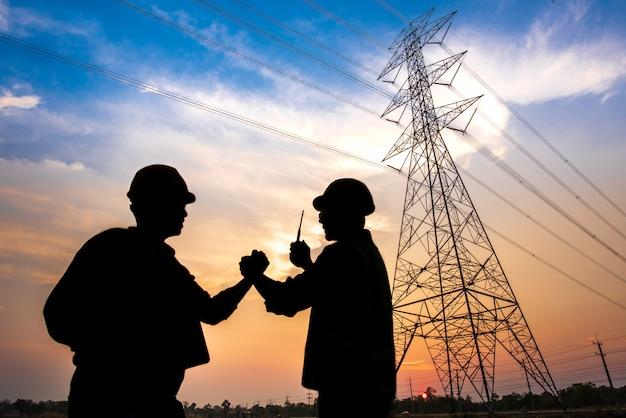 Silhouette von zwei elektrotechnikern, die an einem kraftwerk stehen, das in der luft steht und hände schüttelt, die der erzeugung von elektrischem strom zustimmen.