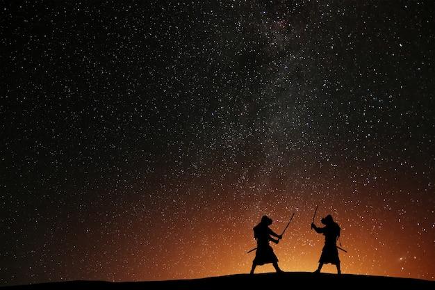 Silhouette von zwei samurais gegen den sternenhimmel. tödliche krieger mit schwertern