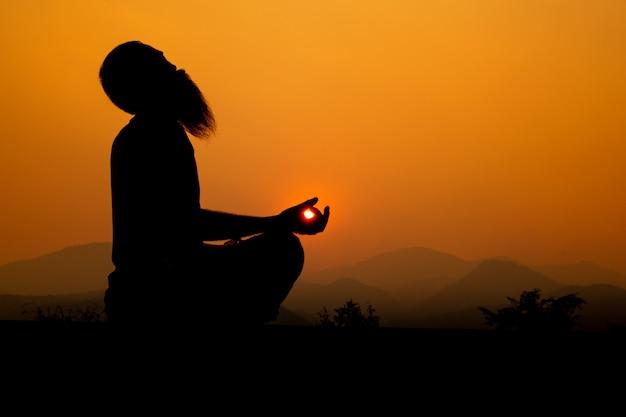 Silhouette - yoga-junge auf dem dach während des sonnenuntergangs, er praktiziert yoga.