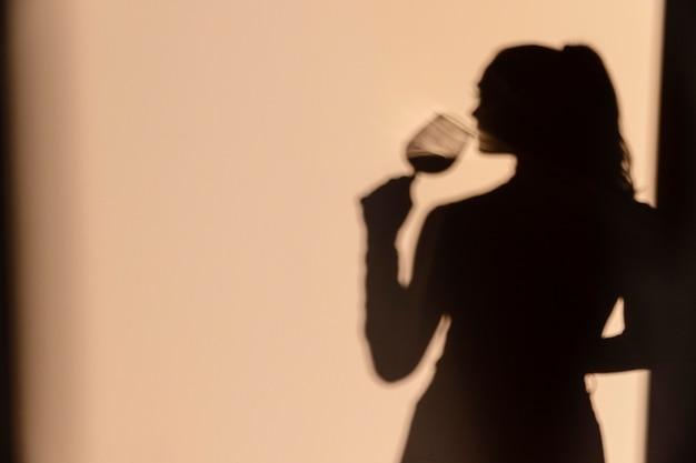 Silhouetten der frau, die wein trinkt
